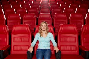 Image of woman sitting alone in a movie theater